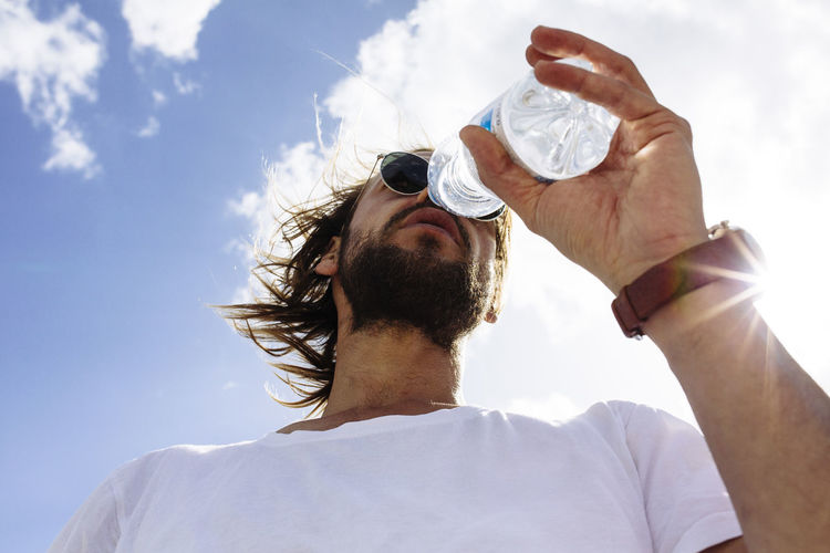 Low angle view of man wearing sunglasses and drinking water against sky