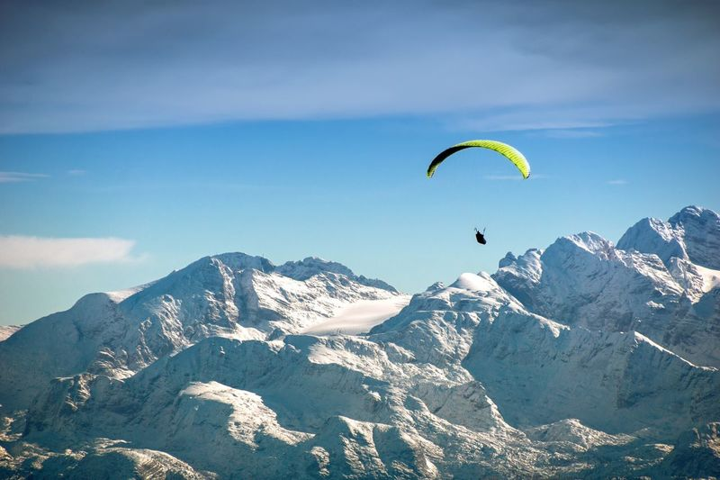 Person Paragliding By Snowcapped Mountains