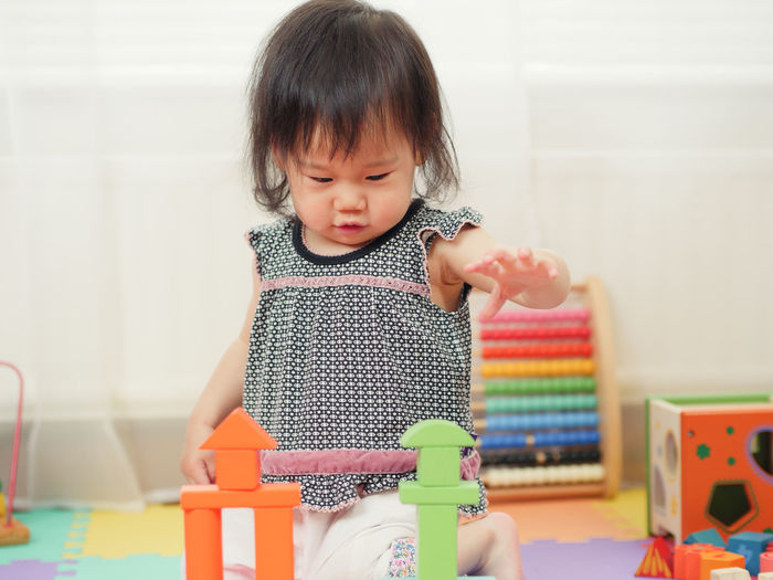 Baby girl playing with toys at home