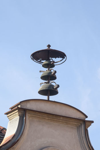 Low angle view of electric lamp by building against sky
