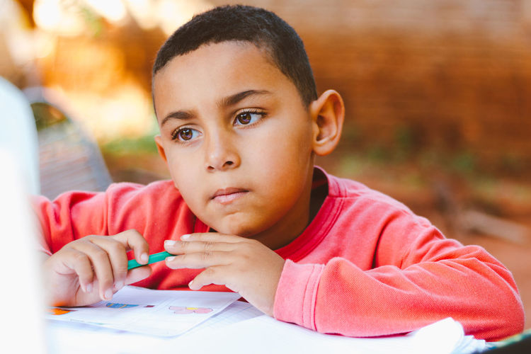Close-up portrait of boy sitting on table