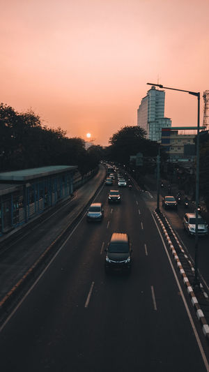Traffic on road at sunset