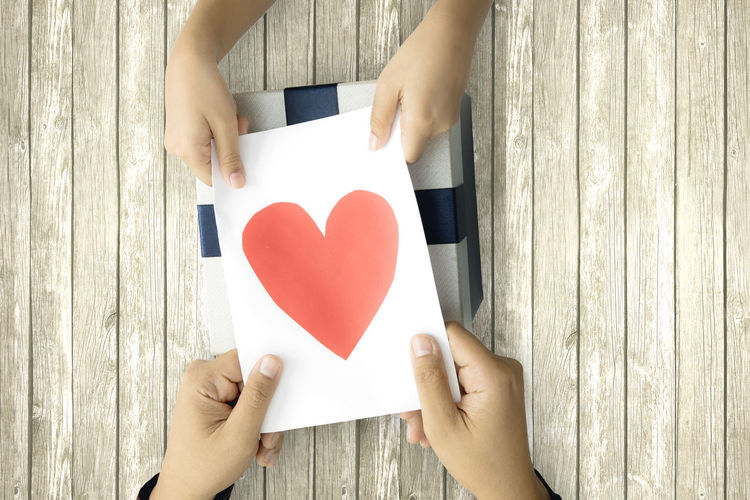 Cropped hands holding heart shape paper over gift on table