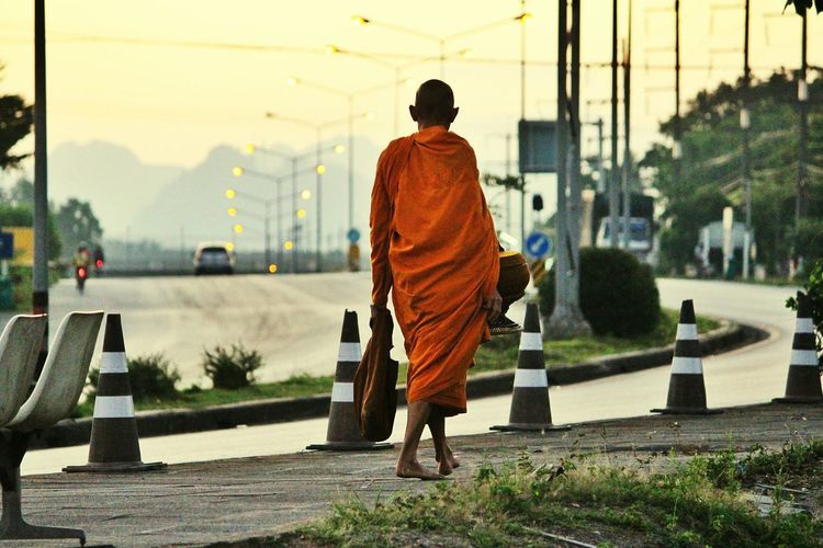 Rear view of monk walking on sidewalk