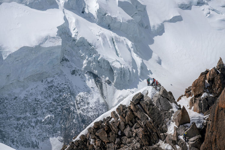 High angle view of people standing on snowcapped mountain