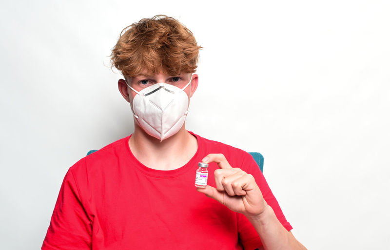 Portrait of person covering face against white background