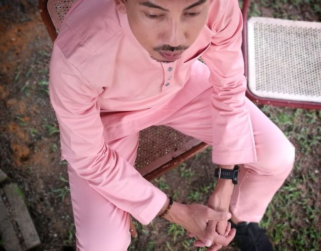 Man in pink traditional clothing sitting on chair