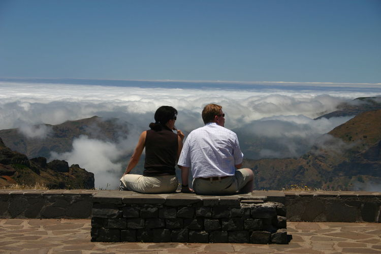 Adult Adults Only Beauty In Nature Day Full Length Leisure Activity Looking At View Madeira Men Mountain Mountains Nature Outdoors People Real People Rear View Scenics Sitting Sky Togetherness Two People
