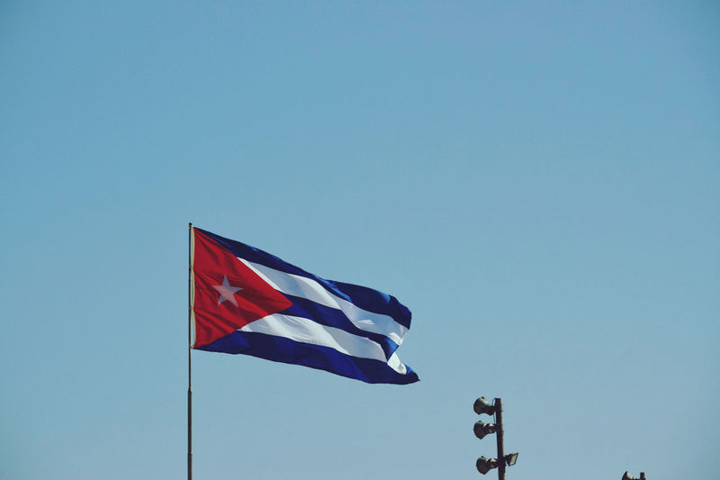 Low angle view of cuban flag against clear blue sky