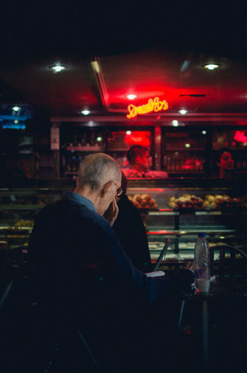 CAFÉ NEONS EyeEm Best Shots EyeEm Selects Adult Bar Counter Business City Food And Drink Illuminated Indoors  Leisure Activity Lifestyles Lighting Equipment Mature Adult Mature Men Men Night Nightclub Nightlife One Person Real People Side View Sitting Streetphotography Waist Up