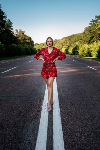 Full length portrait of smiling girl standing on road
