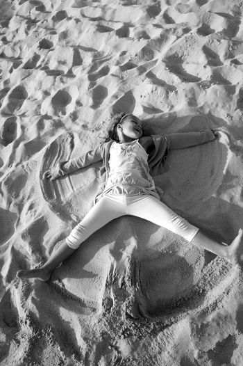 High angle view of little girl making angel in sand at beach