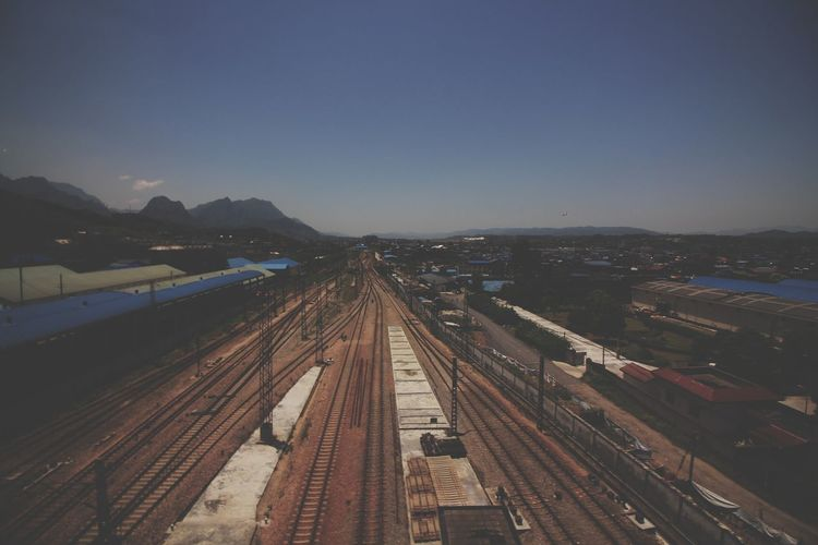 High angle view of railroad tracks in city against clear sky