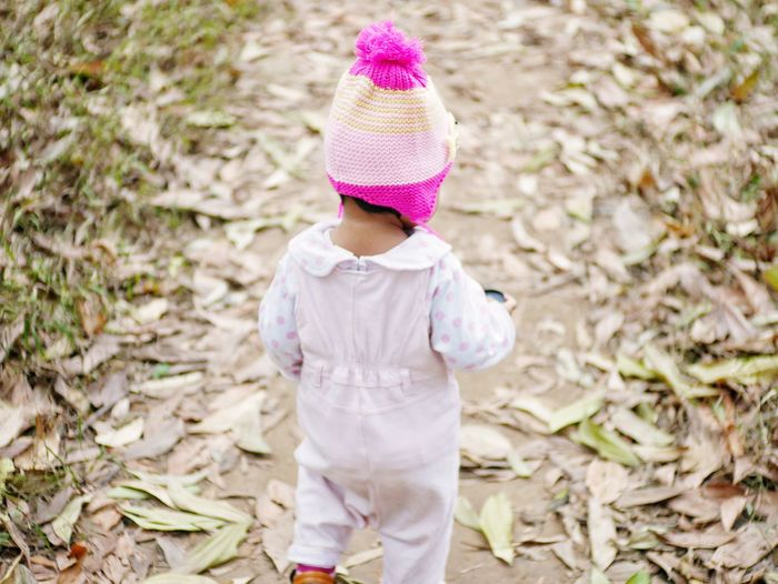 Rear View Of Baby Girl Walking On Field