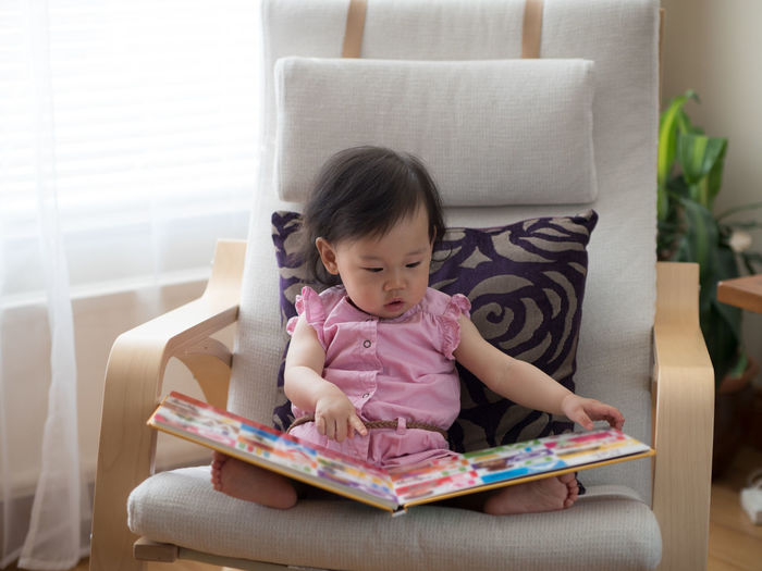 Cute girl sitting on chair and reading book at home