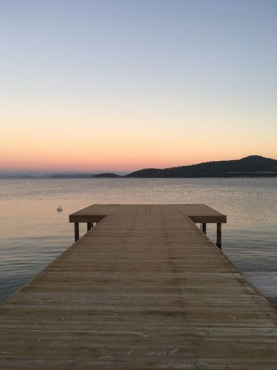 Long Wooden Jetty Overlooking The Sea Sea Water Clear Sky Nature Beauty In Nature Tranquility Tranquil Scene Pier Scenics Wood - Material Idyllic Horizon Over Water No People Boardwalk The Way Forward Sunset Wood Paneling Outdoors Sky Day (null)Spingtime Colours Beach