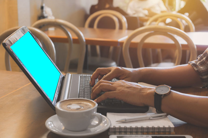 Male using a computer with coffee cup on wooden table. Technology Wireless Technology Cup Drink Communication Mug Coffee Cup Connection Coffee Coffee - Drink Computer Real People Food And Drink Table Refreshment Laptop Human Hand Hand Lifestyles Using Laptop Coffee Shop Crockery