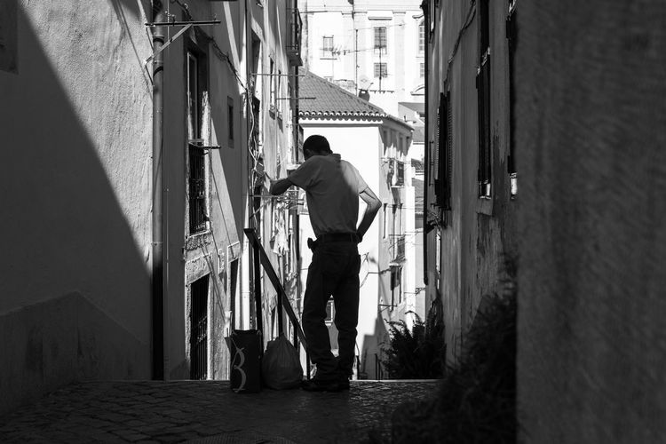 Man standing in alley amidst houses