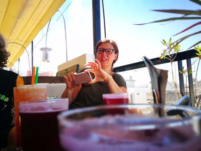 Drinking a casual drik at the rooftop Drink Eyeglasses  Sitting Smiling Drinking Straw Headshot Front View Food And Drink Sky Summer Road Tripping
