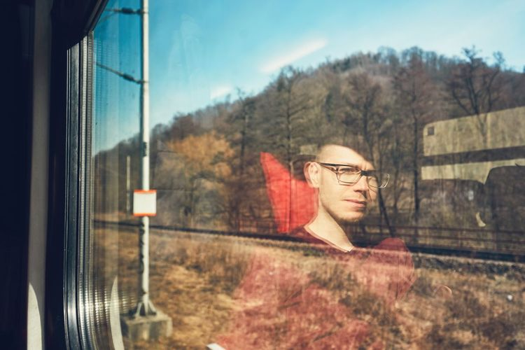Trees Seen Through Window With Reflection Of Man In Train