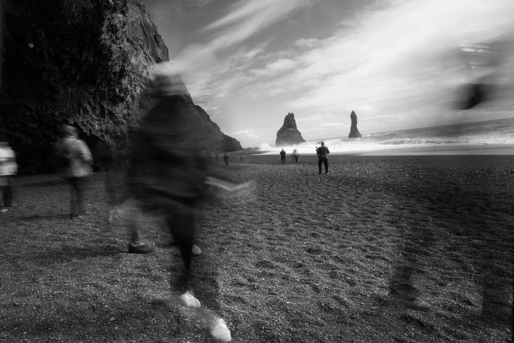 People walking on the black beach of Vik, Iceland Beach Beauty In Nature Black Beach Sand Blackandwhite Cliffs Clouds And Sky Iceland Motion Blur Nature Ocean Peebles People Person Rock Sand Sea Silhouette Sky Tourism Vacations Water