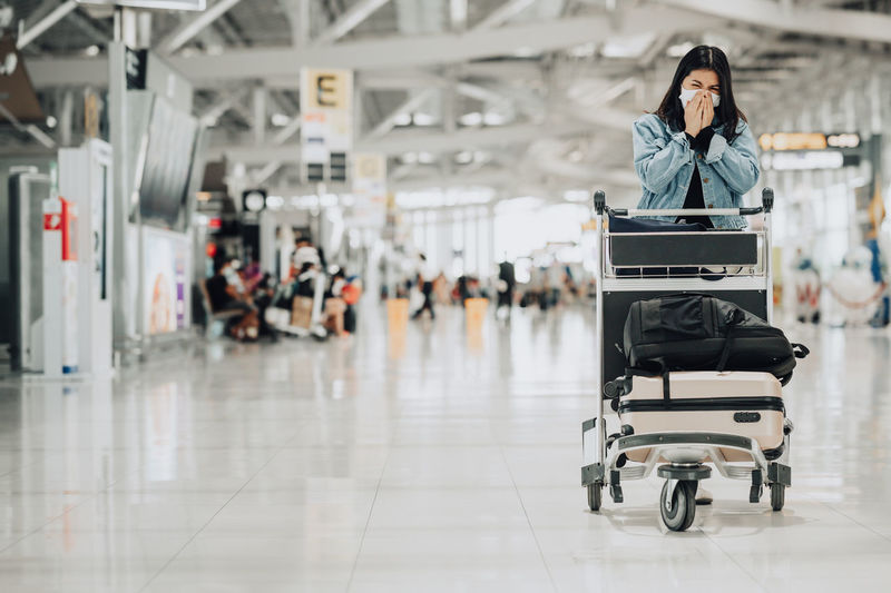 Full length of woman sitting at airport