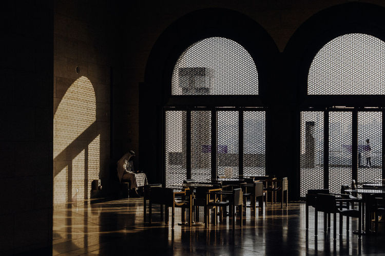 Silhouette people sitting on table by window in building