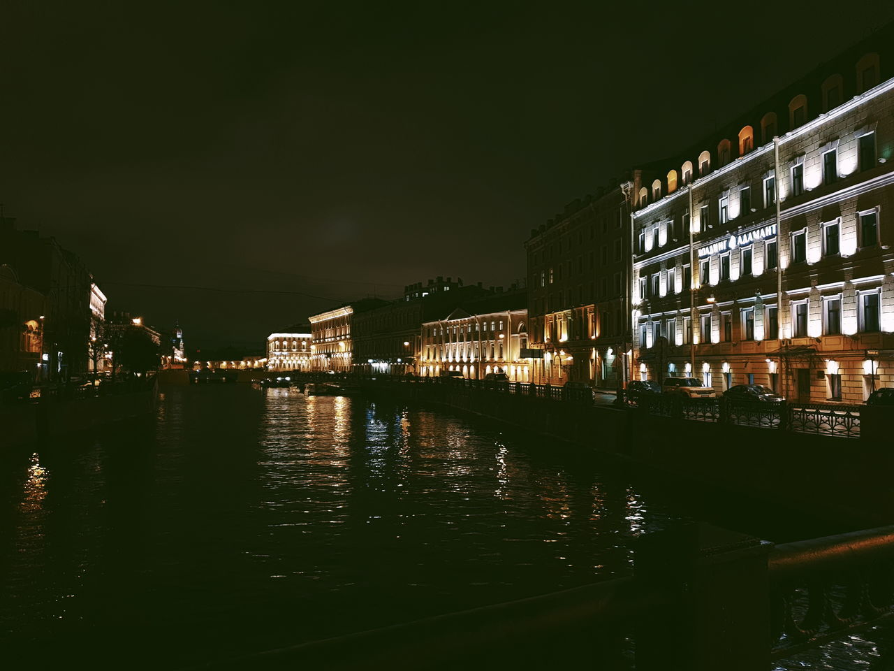 RIVER BY ILLUMINATED BUILDINGS IN CITY AT NIGHT