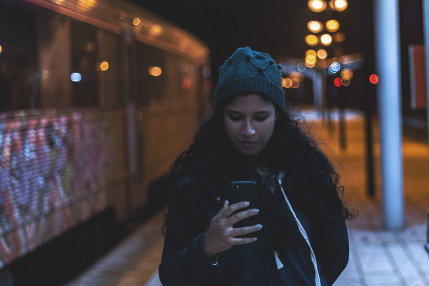Wireless Technology Technology Communication One Person Smart Phone Night Illuminated Portable Information Device Mobile Phone Real People Lifestyles City Holding Warm Clothing Text Messaging Connection Young Adult Using Phone Telephone Clothing Looking Hair Scarf