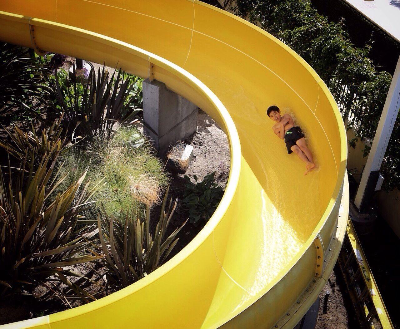 Full length of happy boy on yellow water slide