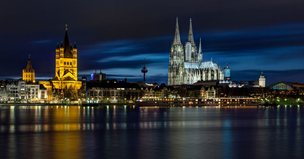 Illuminated buildings and cologne cathedral by rhine river in city at night