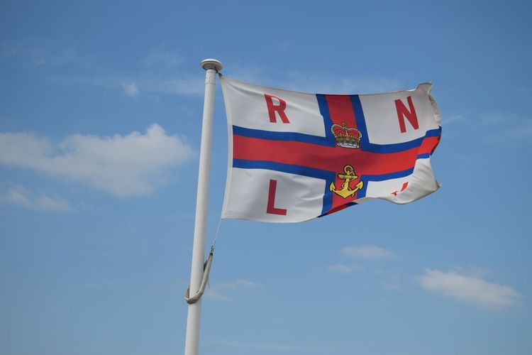 Low angle view of rnli flag against blue sky