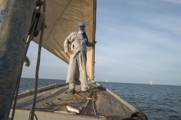 Man Standing On Boat In Sea Against Sky