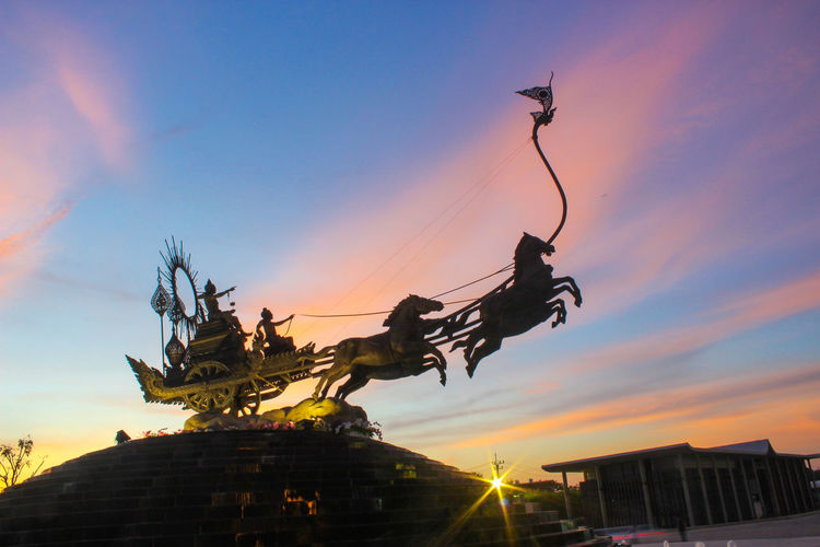 Low angle view of statue against sky during sunset