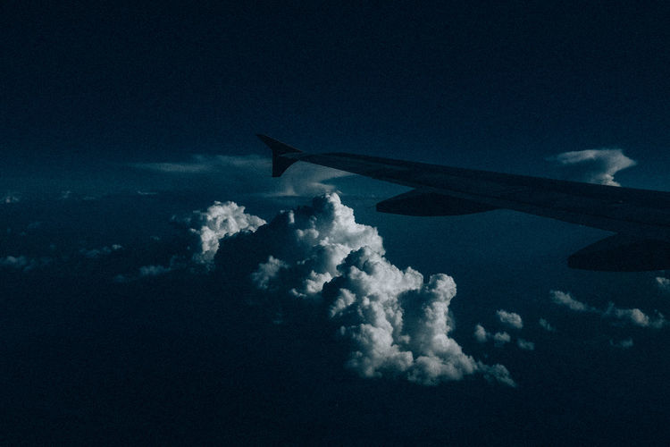 Airplane flying over sea against blue sky