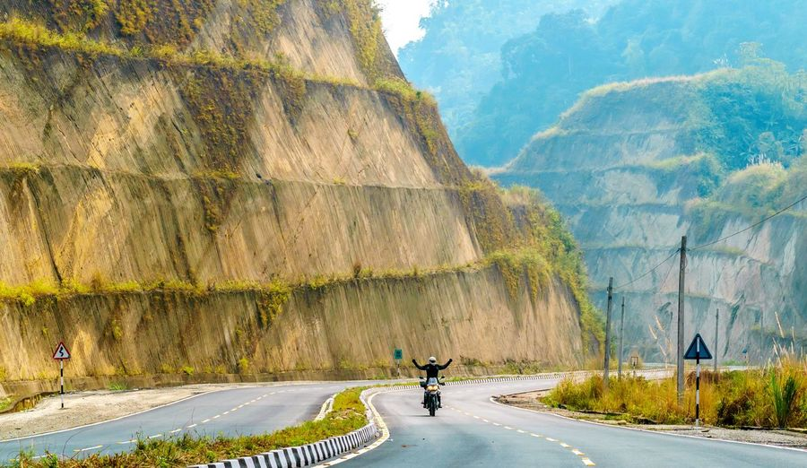 Person riding motorcycle on road by mountain