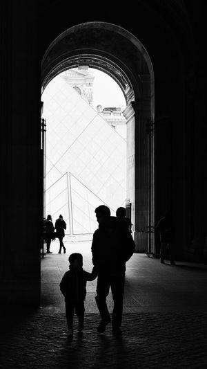 Rear view of silhouette people walking in building