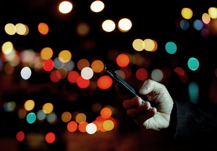 Cropped Hand Of Man Using Mobile Phone Against Illuminated Lights At Night