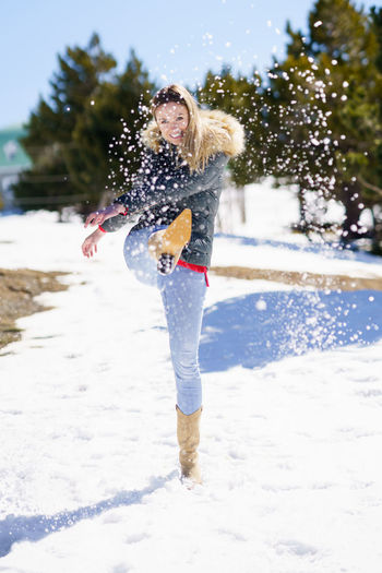 Full length of woman walking in snow during winter