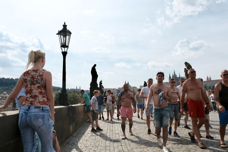 Rear view of people walking on street in city against sky
