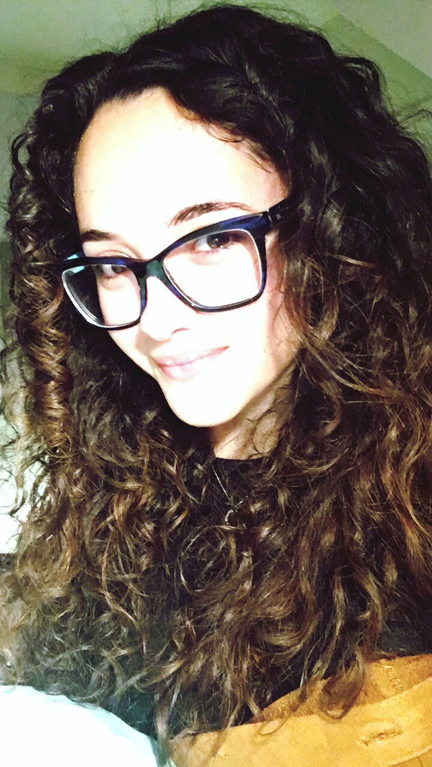 looking at camera, portrait, long hair, real people, young adult, eyeglasses, young women, one person, headshot, close-up, lifestyles, smiling, beautiful woman, curly hair, sunglasses, confidence, indoors, happiness, freckle, day, people, adult