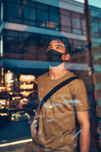 Young man standing in coffee shop at store front in the city center in the evening, wearing the mask