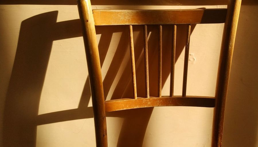 Close-up of wooden chair against wall
