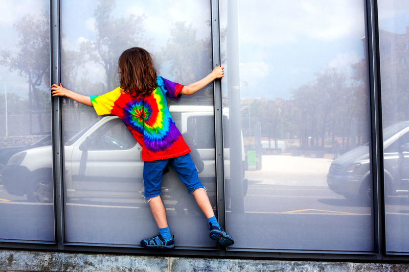 8 year old boy with long hair and tie die t-shirt climbing along a ledge, Barcelona, Spain. Balance Boy Lad Long Hair Pretty Casual Clothing City Climbing Colorful Colors Colour Day Horizontal One Person Playing Shorts Tie Die T-shirt Urban
