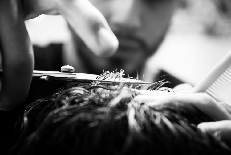 Close-up of barber cutting customer hair