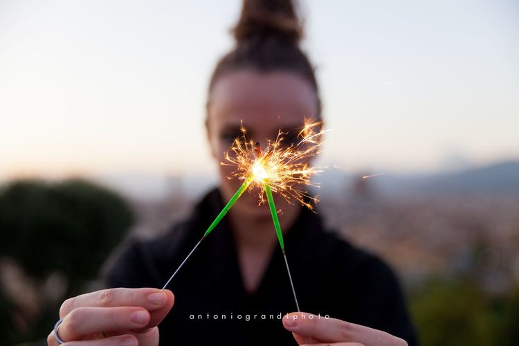 Focus On Foreground Sparkler Holding Human Hand Burning One Person Motion Outdoors Real People Long Exposure Close-up Leisure Activity Sunset Lifestyles Human Body Part Day People