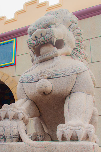 Stone Lion Guardian statue at the entrance gate of Anek Kusala Sala (Viharn Sien), Thai-Chinese temple in Pattaya, Thailand. It was built in 1987 and is one of popular tourist attractions Entrance Entrance Gate Lion Pattaya Statue Viharnra Sien Architecture Art And Craft Building Exterior Built Structure Chinese Temple Close-up Day Entrance Door Guardian Low Angle View No People Outdoors Place Of Worship Sculpture Spirituality Statue Stone Stone Lion Travel Destinations