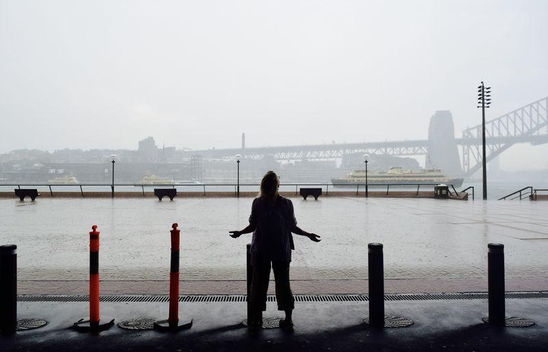 Rear View Of Woman Standing Against Bridge During Rainy Season