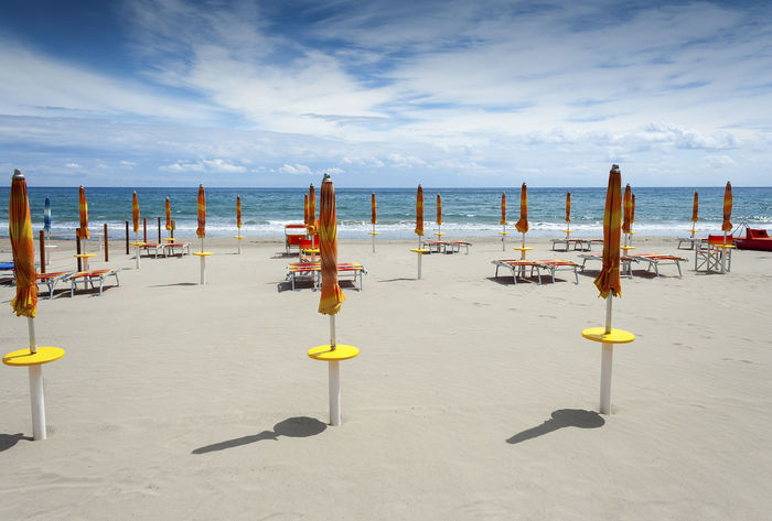 Laigueglia sandy beach in the morning before people have arrived with folded umbrellas, sun loungers with a blue sky and white clouds in Liguria Italy Hot Mediterranean  Morning Sunny Beach Blue Clouds Coast Italy Laigueglia Leisure Liguria No People Ocean Sandy Sea Shore Sky Summer Tourism Tranquility Umbrellas Vacation Water Yellow
