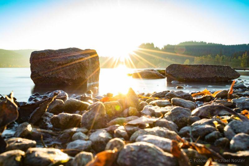 Lens Flare Sunset Sunlight Sunbeam Rock - Object Sun Beach Sea Outdoors No People Landscape Water